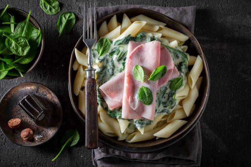 Heerlijke deegwaren met spinazie, ham en bechamel saus stock fotografie