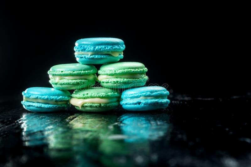 Heerlijke die makarons op zwarte achtergrond worden geïsoleerd Frans zoet koekje stock afbeeldingen