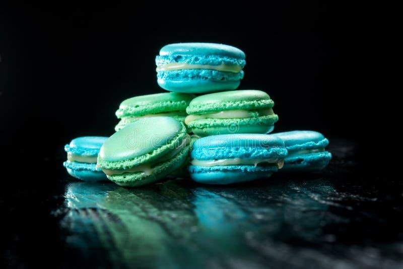 Heerlijke die makarons op zwarte achtergrond worden geïsoleerd Frans zoet koekje stock afbeelding