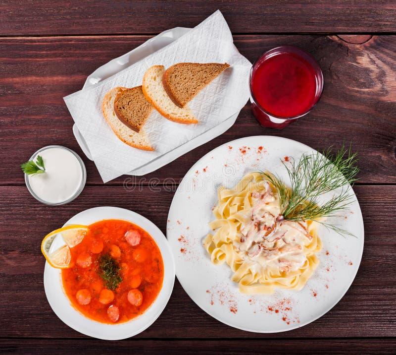Heerlijke dinerlijst met Fettuccine-deegwaren met vlees, hete soep met worsten, brood en compote op houten achtergrond stock fotografie