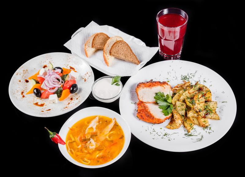 Heerlijke dinerlijst met gebakken kippenborst en aardappels, verse Griekse salade, kippensoep, brood en compote royalty-vrije stock afbeelding