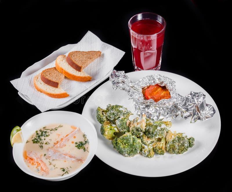 Heerlijke dinerlijst met gebakken vlees en broccoli, vissensoep met zalm en garnaal, brood en compote op zwarte achtergrond stock fotografie