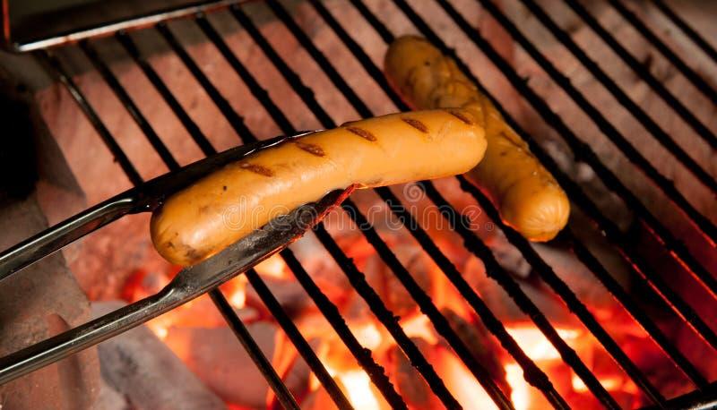 Heerlijke Duitse worsten op de barbecuegrill stock afbeeldingen