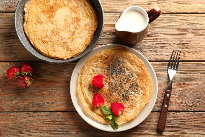 Heerlijke dunne pannekoeken met bessen en melk op houten lijst stock afbeelding