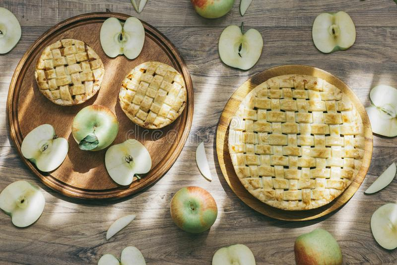 Heerlijke eigengemaakte appeltaarten en reeks gehele verse groene appelen en besnoeiingsappel en plakken in het zachte natuurlijk stock afbeelding
