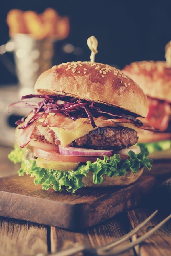 Heerlijke eigengemaakte hamburger op houten achtergrond royalty-vrije stock afbeelding