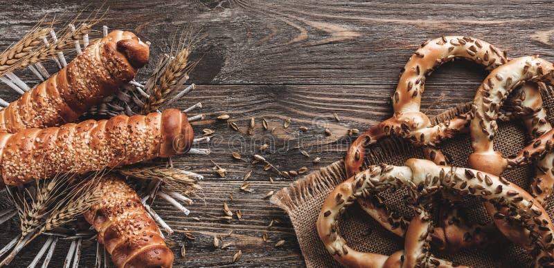 Heerlijke eigengemaakte pretzels voor snack met zonnebloemzaden en worsten in deeg stock fotografie