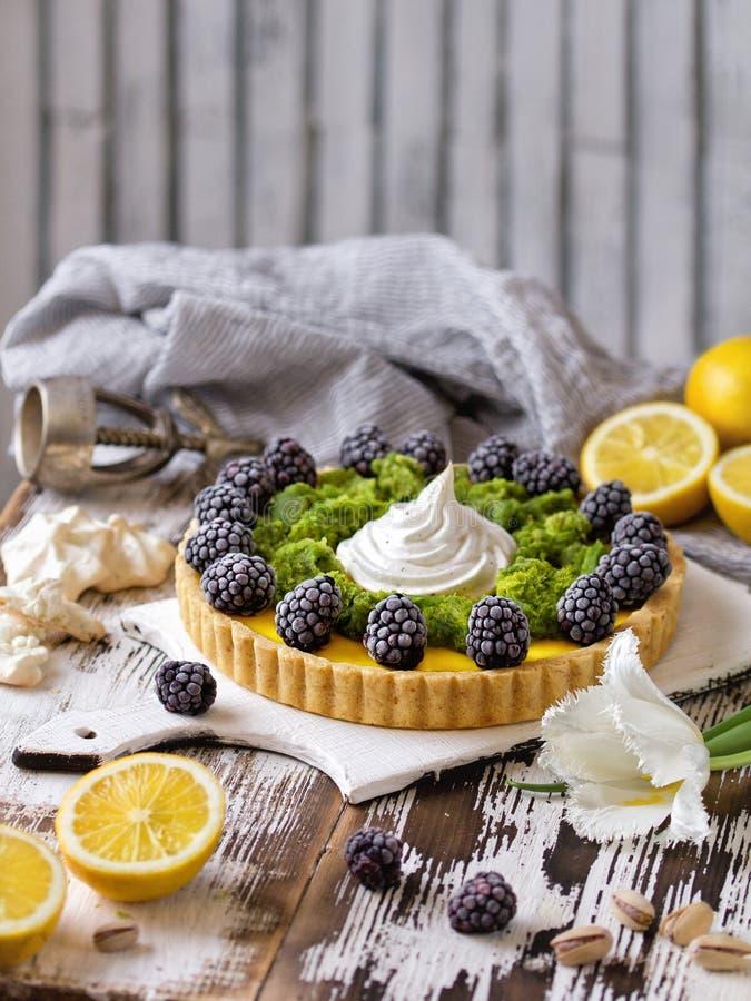 Heerlijke eigengemaakte scherpe citroen Pastei op rustieke witte lijst Scherp met braambes en schuimgebakje royalty-vrije stock afbeelding