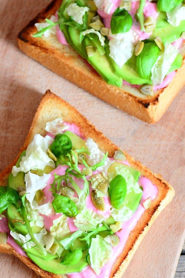 Heerlijke en eenvoudige sandwiches met avocado, sla, basilicum, pompoenzaden en romige roze bietensaus royalty-vrije stock foto