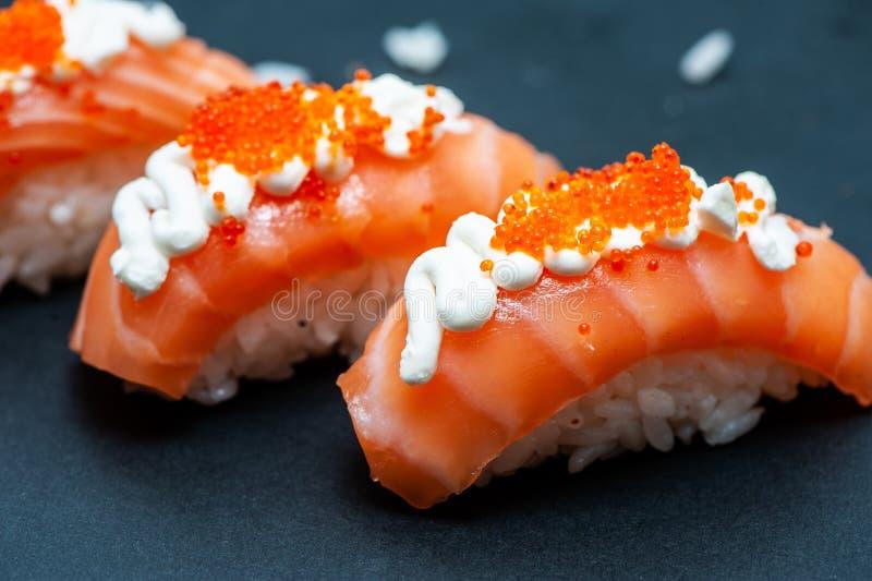 Heerlijke en sappige Sushi met van de zalmrijst en kaviaar close-up op een zwarte stock fotografie