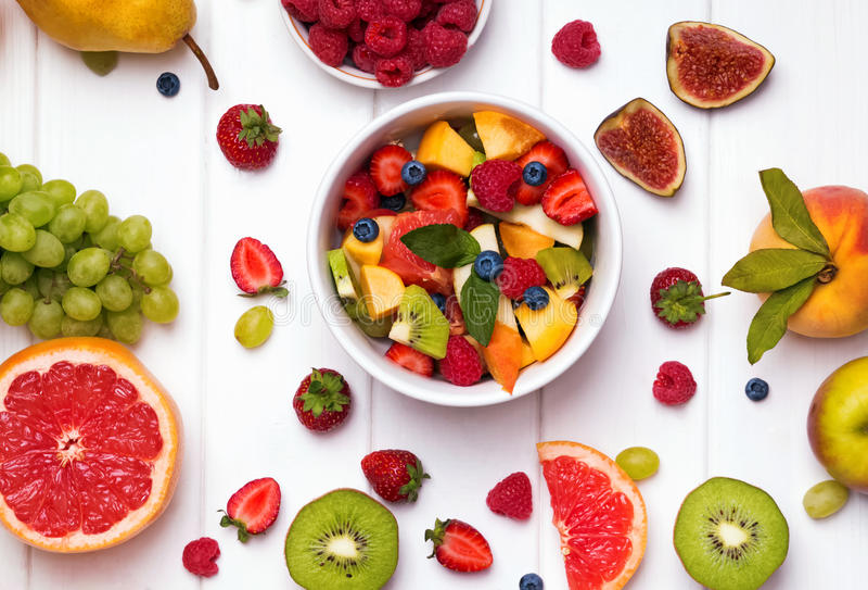 Heerlijke fruitsalade en verschillende vruchten en bessen op wh royalty-vrije stock afbeeldingen