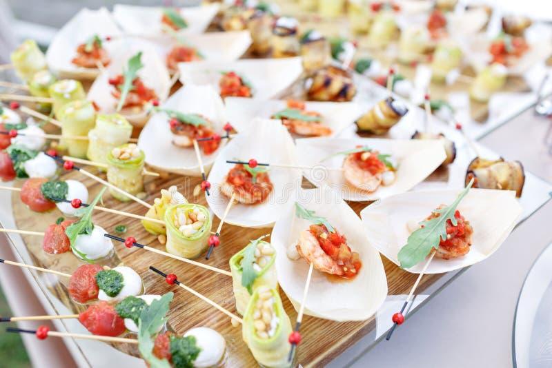 Heerlijke garnalen en gesneden tomaten op een houten boot Courgettebroodjes met pijnboomnoten Smakelijke buffetlijst De zomerpart royalty-vrije stock fotografie