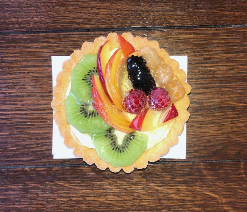 Heerlijke gebakjecake met vers fruit op lijst royalty-vrije stock afbeeldingen