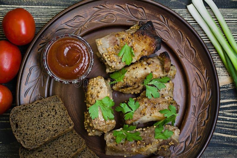 Heerlijke gebraden ribben, gekleed met honingssaus, die met greens en groenten wordt verfraaid stock foto's