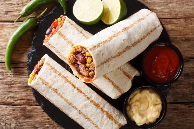 Heerlijke geroosterde die burrito met fijngehakt rundvlees, bonen, graan wordt gevuld, stock afbeelding