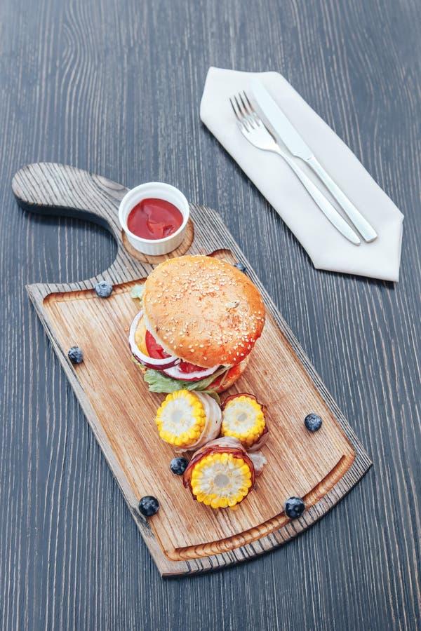 Heerlijke geroosterde eigengemaakte hamburger met rundvlees, ui, tomaat, kaas, salade en graan BBQ Hamburgers stock afbeelding