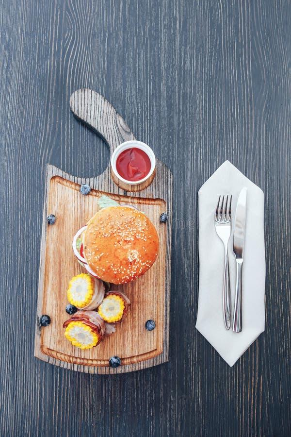 Heerlijke geroosterde eigengemaakte hamburger met rundvlees, ui, tomaat, kaas, salade en graan BBQ Hamburgers royalty-vrije stock afbeeldingen