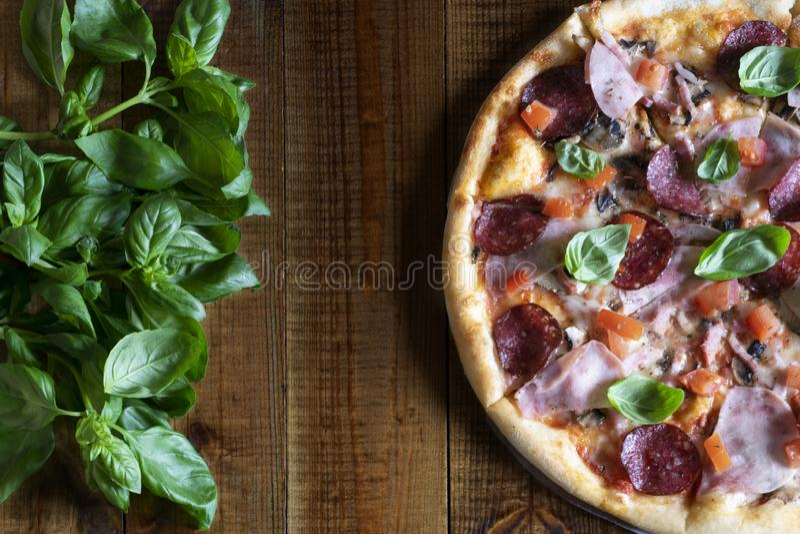 Heerlijke geurige pizza met paddestoelen, salami, ham, tomaten, mozarella en vers Basilicum op een houten lijst royalty-vrije stock foto's
