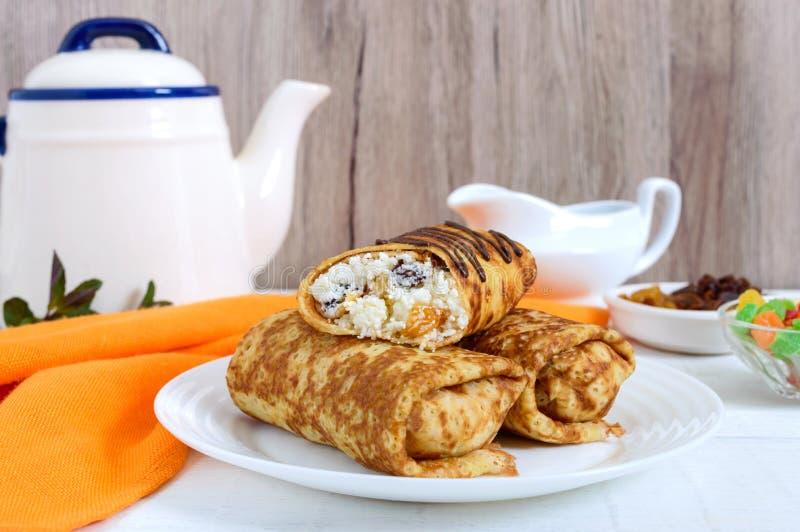 Heerlijke gevoelige pannekoeken met kwark en rozijnen op een witte houten achtergrond Gezond Ontbijt royalty-vrije stock foto's