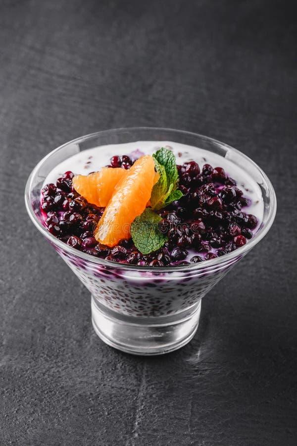 Heerlijke granola met yoghurt, verse bessen, vruchten in glas op zwarte achtergrond stock foto