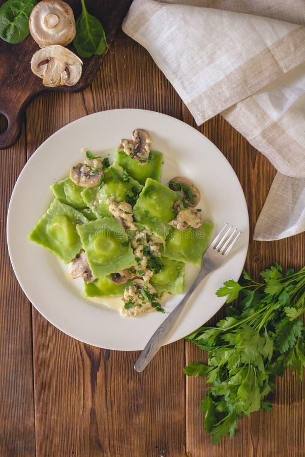 Heerlijke groene die bollen met spinaziedeeg met kaas met champignonsaus wordt gevuld Italiaanse keuken stock afbeelding