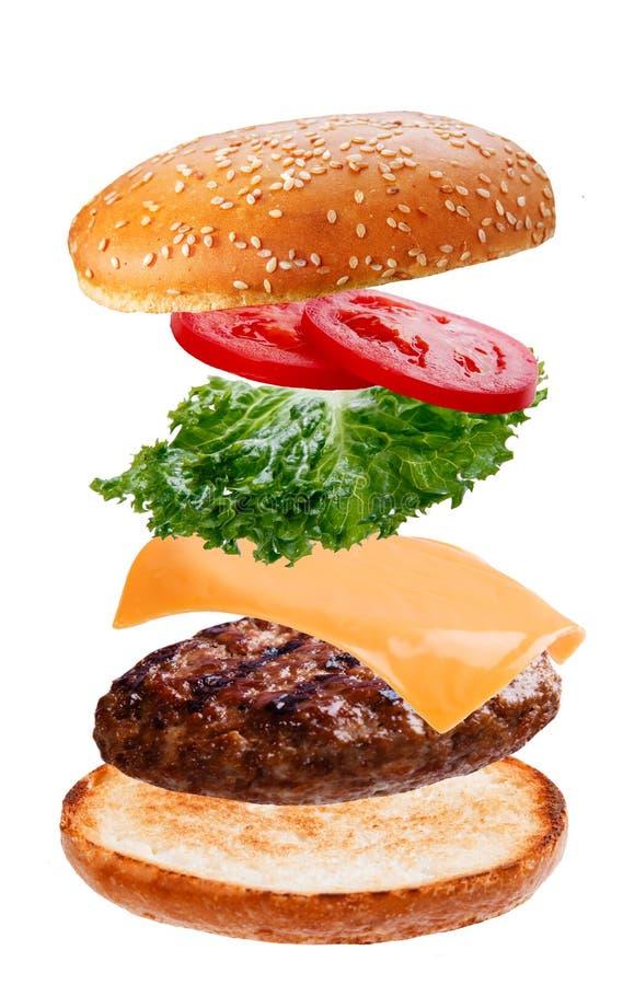 Heerlijke hamburger met vliegende dalende ingrediënten op witte achtergrond stock afbeelding