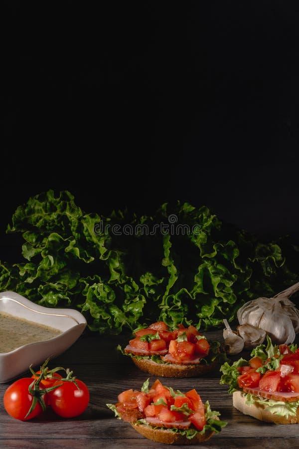 Heerlijke Italiaanse antipastibruschetta met gehakte tomaat, vleespastei, saus, roomkaas en salade gaat weg Reeks van smakelijk stock foto