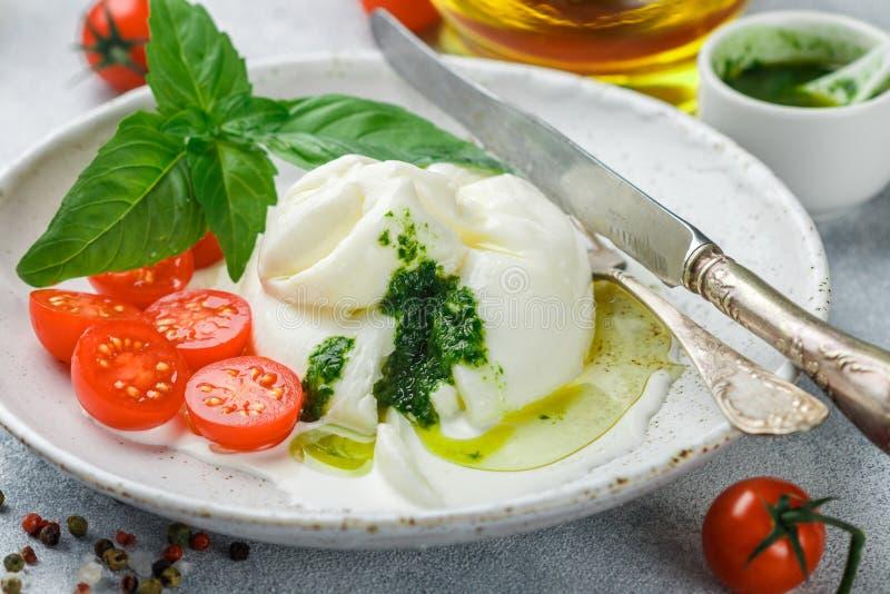 Heerlijke Italiaanse verse burratakaas met kersentomaten, Basilicumpesto en olijfolie stock fotografie