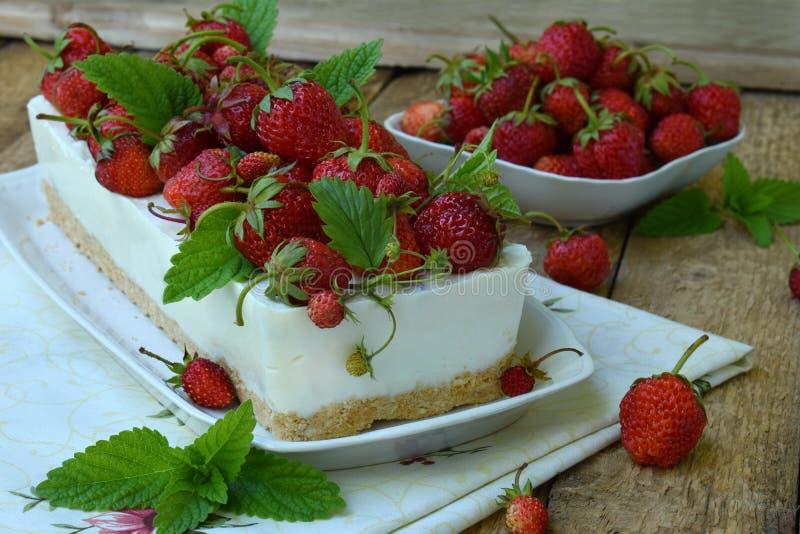 Heerlijke kaastaart met bessen, bio eigengemaakte aardbeien van tuin, heerlijke en eenvoudige cake op houten achtergrond stock afbeelding