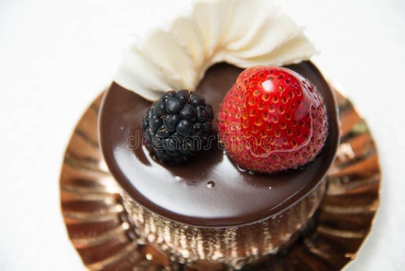 Heerlijke kleine chocoladecake met sommige vruchten op bovenkant stock afbeeldingen