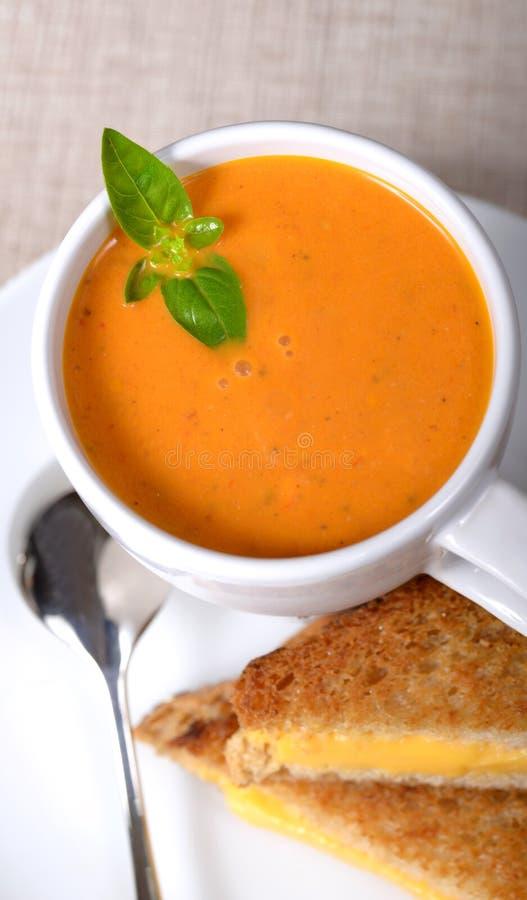 Heerlijke kom tomatensoep met geroosterde kaassandwich stock foto's
