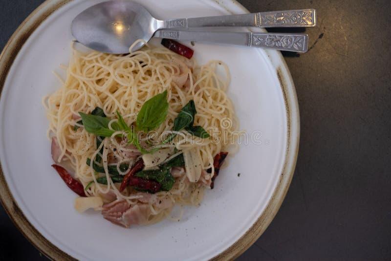 Heerlijke kruidige spaghetti met bacon, droge Spaanse pepers, basilicum en knoflook met vork en lepel royalty-vrije stock foto
