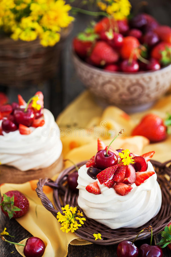 Heerlijke minidiePavlova-schuimgebakjecake met verse berrie wordt verfraaid stock afbeeldingen