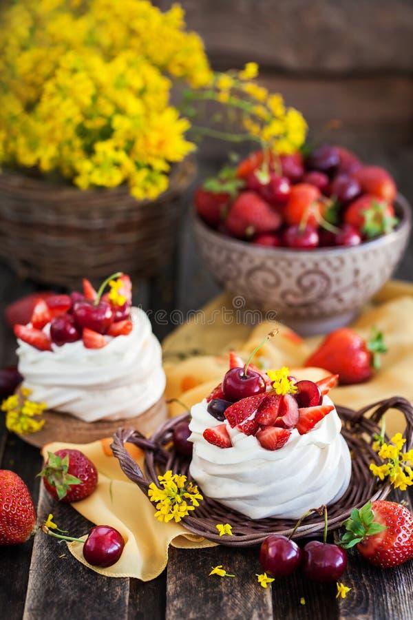 Heerlijke minidiePavlova-schuimgebakjecake met verse berrie wordt verfraaid stock foto's