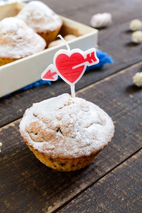 Heerlijke muffin met gepoederde suiker en een hart-vormige kaars op een houten lijst Feestelijke Cakes stock fotografie