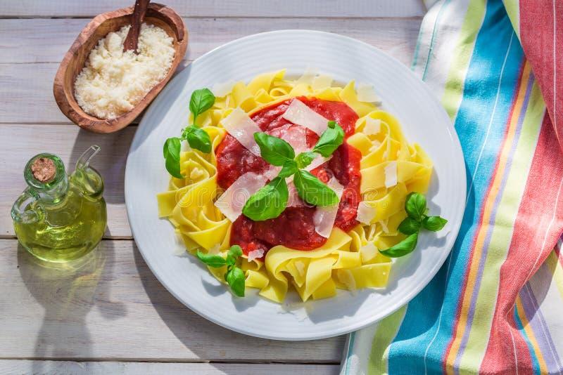 Heerlijke pappardelledeegwaren met tomaat, basilicum en parmezaanse kaas stock fotografie