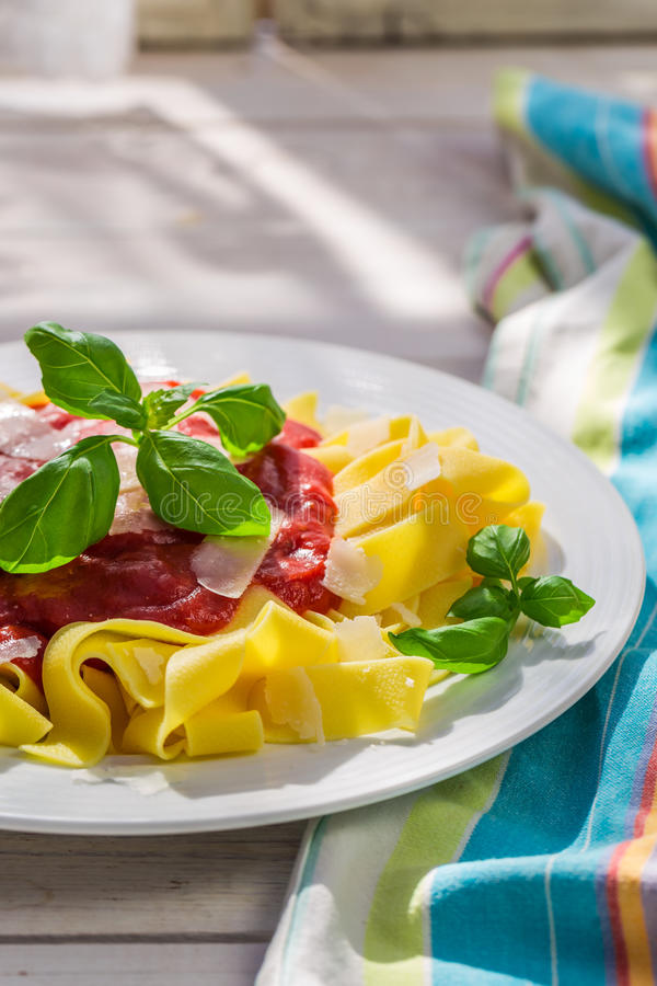 Heerlijke pappardelledeegwaren met tomatensaus en parmezaanse kaas stock afbeeldingen