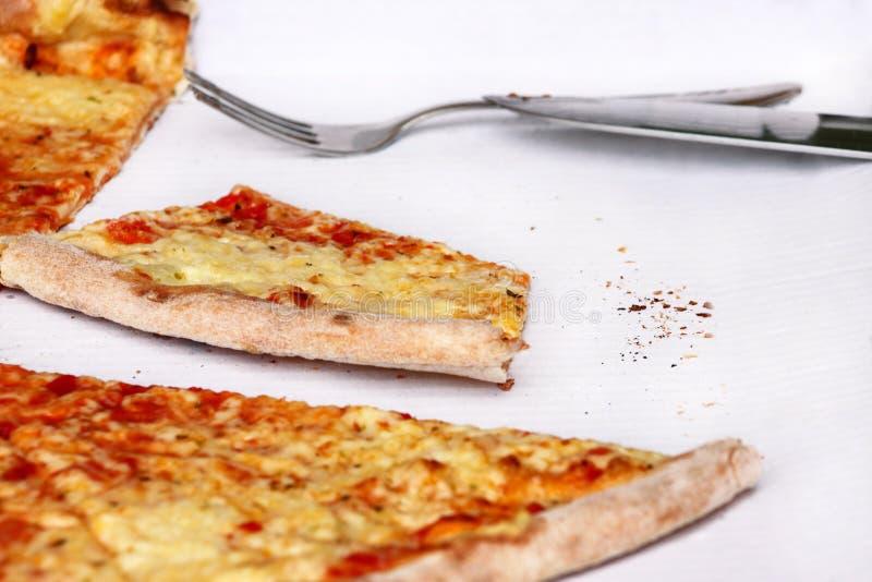 Heerlijke pizza Margarita en plakken van pizza, vork en mes Italiaanse traditionele klassieke pizza die in een doos worden gehoud stock foto's
