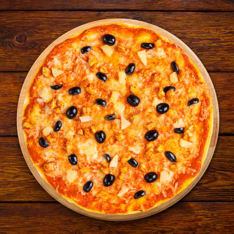 Heerlijke pizza met ananas, kip en olijven stock foto's