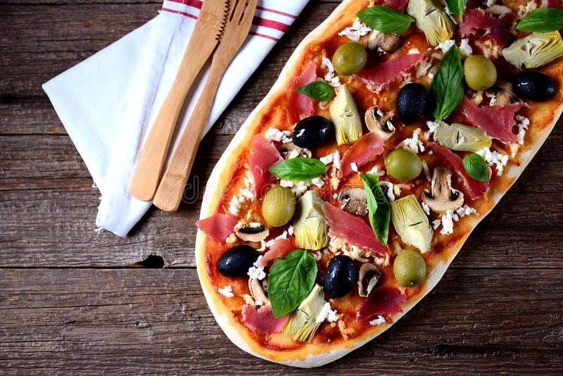 Heerlijke pizza met artisjokken, olijven, jamon hamon, paddestoelen, kaas en basilicum op een houten achtergrond royalty-vrije stock afbeelding