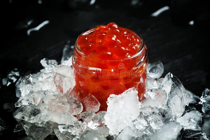 Heerlijke rode kaviaar in een glaskruik op verpletterd ijs op zwarte ston royalty-vrije stock foto's