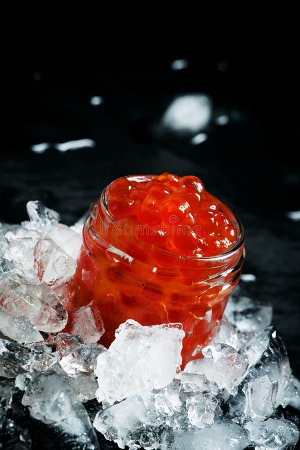 Heerlijke rode kaviaar in een glaskruik op verpletterd ijs op zwarte ston royalty-vrije stock afbeeldingen