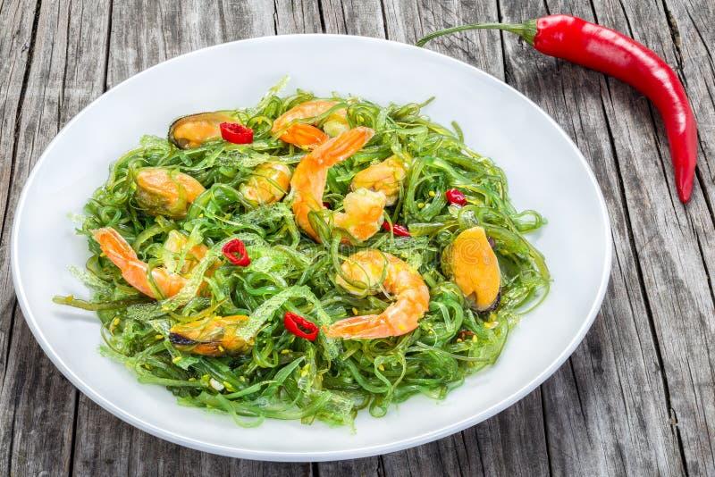 Heerlijke salade van garnalen, mosselen, zeewier, Spaanse pepers en sesam die zich met extra eerste persing op de witte schotel o stock foto
