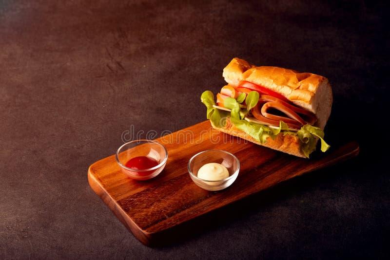 Heerlijke sandwich met ham, tomaat, arugula samen met tomatensaus en mayonaise stock afbeelding