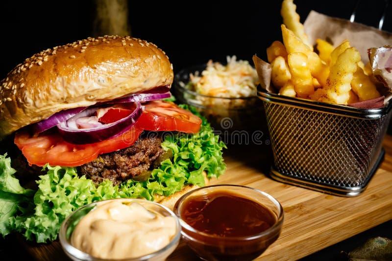 heerlijke sappige rundvleeshamburger, Amerikaans stijlvoedsel met frieten en koolslasalade stock foto