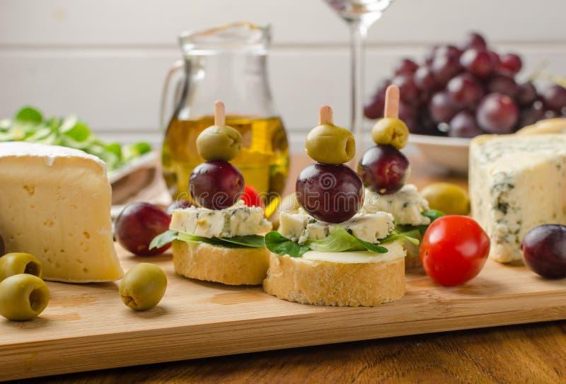 Heerlijke schimmelkaas met olijven, druiven en salade stock afbeelding