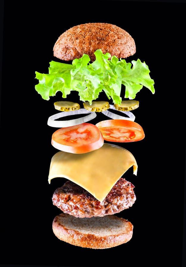 Heerlijke smakelijke hamburger met vliegende die ingrediënten op zwarte achtergrond worden geïsoleerd Hamburgerdelen die in lucht stock afbeelding