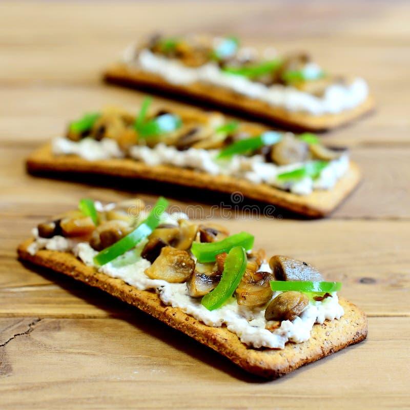 Heerlijke snack met paddestoelen en groenten Gebraden paddestoelen en verse groene groene paprika op dunne crackers royalty-vrije stock foto