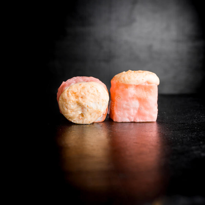 Heerlijke sushibroodjes op zwarte achtergrond Japans voedsel stock foto's