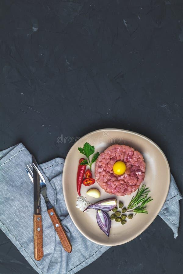 Heerlijke tartaar met dooier en ingrediënten op ceramische plaat royalty-vrije stock foto